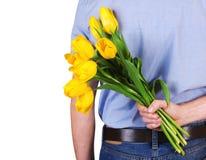 Le dos de l'homme avec les tulipes jaunes Image libre de droits