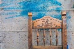 Le dos de la vieille chaise en bois sur le mur en béton de fond avec des taches de peinture bleue (clo Photos stock