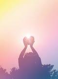 Le dos de silhouette des femmes soulèvent le haert au ciel au crépuscule Image stock