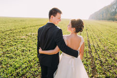 Le dos des nouveaux mariés étreignants et de sourires passant leur temps dans le domaine Images libres de droits