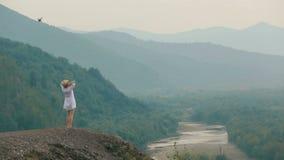 Le dos luttent l'hélicoptère de wfrom sur le beau voyageur blond se tenant au bord des montagnes et appréciant le paysage banque de vidéos