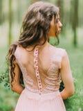 Le dos nu décoré de la dentelle de la femme avec de longs cheveux bouclés dans la robe rose Photo en gros plan dans le bois vert Image libre de droits
