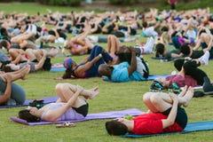 Le dozzine avvolgono la posa di funzionamento alla classe all'aperto di yoga di Atlanta immagine stock libera da diritti