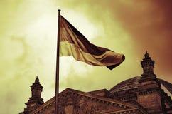 Le drapeau allemand vole au-dessus du bâtiment de Reichstag à Berlin Photographie stock libre de droits