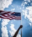 Le drapeau américain avec la bannière étoilée se tiennent avec des mains contre bleu Image libre de droits