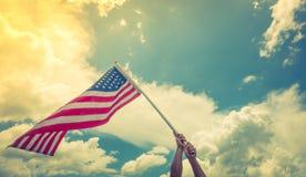 Le drapeau américain avec la bannière étoilée se tiennent avec des mains contre bleu Photos libres de droits