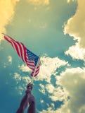 Le drapeau américain avec la bannière étoilée se tiennent avec des mains contre bleu Photographie stock