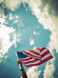 Le drapeau américain avec la bannière étoilée se tiennent avec des mains contre bleu Images libres de droits