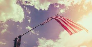 Le drapeau américain avec la bannière étoilée se tiennent avec des mains contre bleu Photo libre de droits