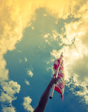 Le drapeau américain avec la bannière étoilée se tiennent avec des mains contre bleu Photographie stock libre de droits