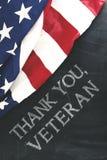 Le drapeau américain près de l'écriture de vous remercient, vétéran Images libres de droits