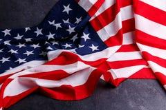 Le drapeau américain se trouve diagonalement sur un fond gris image stock