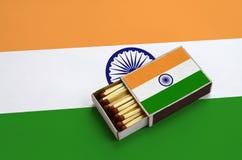 Le drapeau d'Inde est montré dans une boîte d'allumettes ouverte, qui est remplie de matchs et se trouve sur un grand drapeau photos libres de droits