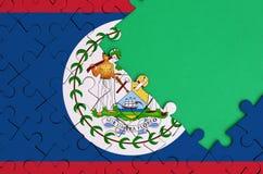 Le drapeau de Belize est dépeint sur un puzzle denteux réalisé avec l'espace vert gratuit de copie du côté droit photo stock