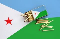 Le drapeau de Djibouti est montré sur une boîte d'allumettes ouverte, de laquelle plusieurs matchs tombent et des mensonges sur u photographie stock