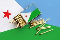 Le drapeau de Djibouti est montré sur une boîte d'allumettes ouverte, de laquelle plusieurs matchs tombent et des mensonges sur u photos libres de droits