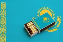 Le drapeau de Kazakhstan est montré dans une boîte d'allumettes ouverte, qui est remplie de matchs et se trouve sur un grand drap image libre de droits