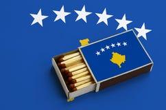 Le drapeau de Kosovo est montré dans une boîte d'allumettes ouverte, qui est remplie de matchs et se trouve sur un grand drapeau image libre de droits