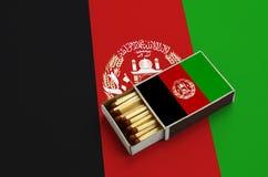 Le drapeau de l'Afghanistan est montré dans une boîte d'allumettes ouverte, qui est remplie de matchs et se trouve sur un grand d image libre de droits
