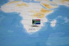 Le drapeau de l'Afrique du Sud dans la carte du monde photo stock