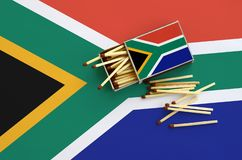 Le drapeau de l'Afrique du Sud est montré sur une boîte d'allumettes ouverte, de laquelle plusieurs matchs tombent et des mensong images libres de droits