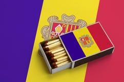 Le drapeau de l'Andorre est montré dans une boîte d'allumettes ouverte, qui est remplie de matchs et se trouve sur un grand drape image stock