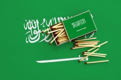 Le drapeau de l'Arabie Saoudite est montré sur une boîte d'allumettes ouverte, de laquelle plusieurs matchs tombent et des menson photo libre de droits