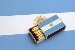 Le drapeau de l'Argentine est montré dans une boîte d'allumettes ouverte, qui est remplie de matchs et se trouve sur un grand dra photographie stock libre de droits