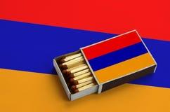 Le drapeau de l'Arménie est montré dans une boîte d'allumettes ouverte, qui est remplie de matchs et se trouve sur un grand drape image libre de droits