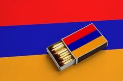Le drapeau de l'Arménie est montré dans une boîte d'allumettes ouverte, qui est remplie de matchs et se trouve sur un grand drape photographie stock