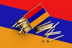 Le drapeau de l'Arménie est montré sur une boîte d'allumettes ouverte, de laquelle plusieurs matchs tombent et des mensonges sur  photographie stock