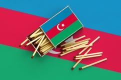 Le drapeau de l'Azerbaïdjan est montré sur une boîte d'allumettes ouverte, de laquelle plusieurs matchs tombent et des mensonges  photos libres de droits