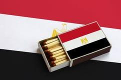 Le drapeau de l'Egypte est montré dans une boîte d'allumettes ouverte, qui est remplie de matchs et se trouve sur un grand drapea image libre de droits
