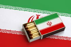 Le drapeau de l'Iran est montré dans une boîte d'allumettes ouverte, qui est remplie de matchs et se trouve sur un grand drapeau photos stock