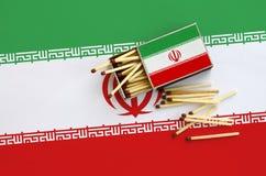 Le drapeau de l'Iran est montré sur une boîte d'allumettes ouverte, de laquelle plusieurs matchs tombent et des mensonges sur un  image stock