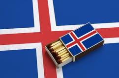 Le drapeau de l'Islande est montré dans une boîte d'allumettes ouverte, qui est remplie de matchs et se trouve sur un grand drape photos stock
