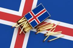 Le drapeau de l'Islande est montré sur une boîte d'allumettes ouverte, de laquelle plusieurs matchs tombent et des mensonges sur  photographie stock