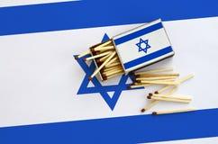 Le drapeau de l'Israël est montré sur une boîte d'allumettes ouverte, de laquelle plusieurs matchs tombent et des mensonges sur u photos libres de droits