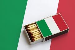 Le drapeau de l'Italie est montré dans une boîte d'allumettes ouverte, qui est remplie de matchs et se trouve sur un grand drapea images libres de droits