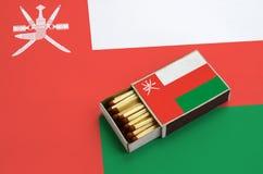 Le drapeau de l'Oman est montré dans une boîte d'allumettes ouverte, qui est remplie de matchs et se trouve sur un grand drapeau photo libre de droits