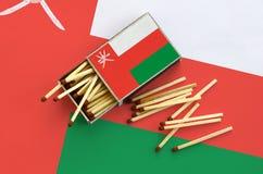 Le drapeau de l'Oman est montré sur une boîte d'allumettes ouverte, de laquelle plusieurs matchs tombent et des mensonges sur un  images stock