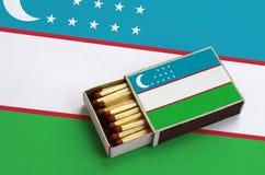Le drapeau de l'Ouzbékistan est montré dans une boîte d'allumettes ouverte, qui est remplie de matchs et se trouve sur un grand d photos stock