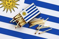 Le drapeau de l'Uruguay est montré sur une boîte d'allumettes ouverte, de laquelle plusieurs matchs tombent et des mensonges sur  images libres de droits