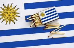 Le drapeau de l'Uruguay est montré sur une boîte d'allumettes ouverte, de laquelle plusieurs matchs tombent et des mensonges sur  image libre de droits