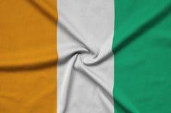 Le drapeau de la Côte d'Ivoire est dépeint sur un tissu de tissu de sports avec beaucoup de plis Bannière d'équipe de sport images stock