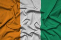 Le drapeau de la Côte d'Ivoire est dépeint sur un tissu de tissu de sports avec beaucoup de plis Bannière d'équipe de sport image stock