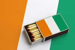Le drapeau de la Côte d'Ivoire est montré dans une boîte d'allumettes ouverte, qui est remplie de matchs et se trouve sur un gran images libres de droits