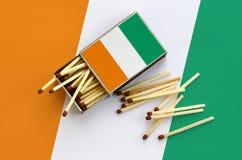 Le drapeau de la Côte d'Ivoire est montré sur une boîte d'allumettes ouverte, de laquelle plusieurs matchs tombent et des mensong images libres de droits