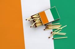 Le drapeau de la Côte d'Ivoire est montré sur une boîte d'allumettes ouverte, de laquelle plusieurs matchs tombent et des mensong photos libres de droits