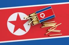 Le drapeau de la Corée du Nord est montré sur une boîte d'allumettes ouverte, de laquelle plusieurs matchs tombent et des mensong image libre de droits